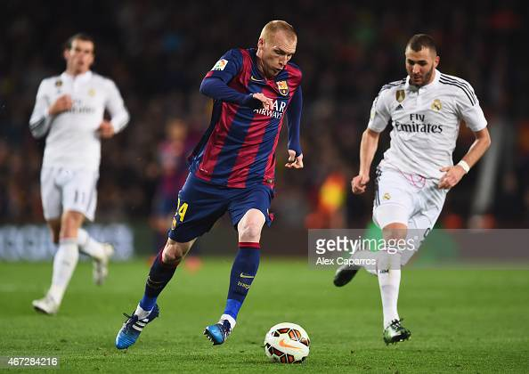 Karim Benzema of Real Madrid CF chases Jeremy Mathieu of Barcelona during the La Liga match between FC Barcelona and Real Madrid CF at Camp Nou on...