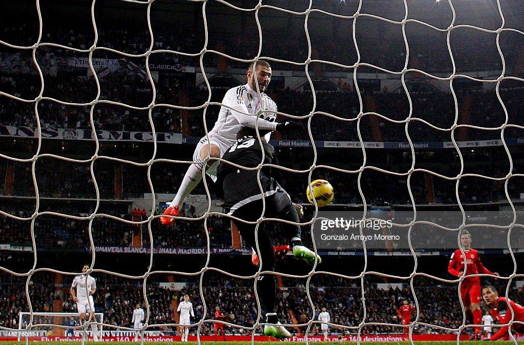 Karim Benzema of Real Madrid CF clashes with goalkeeper Beto of Sevilla FC during the La Liga match between Real Madrid CF and Sevilla FC at Estadio...