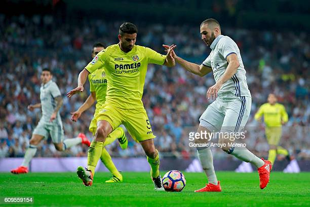 Karim Benzema of Real Madrid CF competes for the ball with Mateo Pablo Musacchio of Villarreal CF during the La Liga match between Real Madrid CF and...