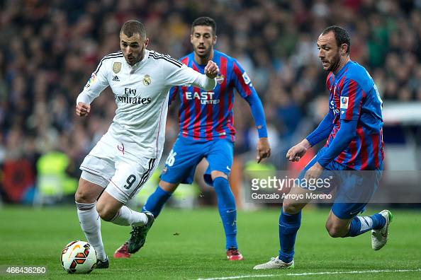 Karim Benzema of Real Madrid CF competes for the ball with Victor Camarasa of Levante UD and his teammate Ivan Ramis during the La Liga match between...