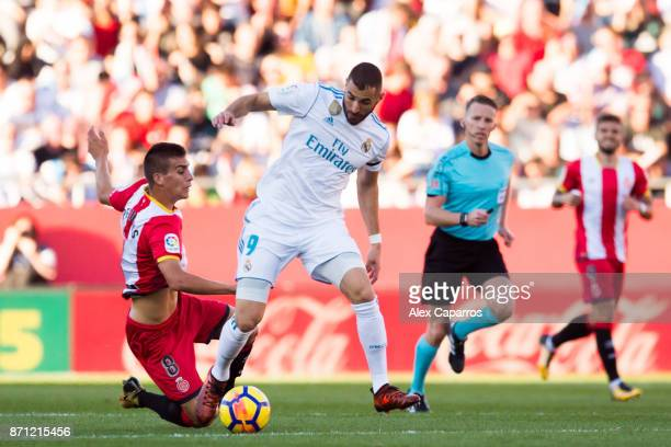 Karim Benzema of Real Madrid CF conducts the ball past Pere Pons of Girona FC during the La Liga match between Girona and Real Madrid at Estadi de...