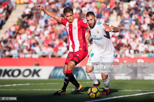 Karim Benzema of Real Madrid CF controls the ball under pressure from Marc Muniesa of Girona FC during the La Liga match between Girona and Real...