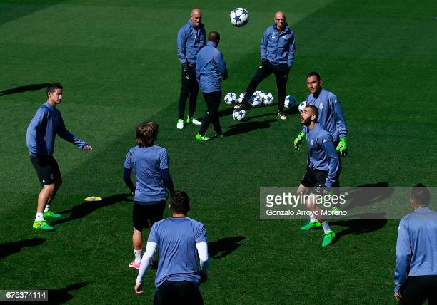 Karim Benzema of Real Madrid CF excersises with his teammates goalkeeper Keylor Navas Luka Modric and James Rodriguez ahead their coach Zinedine...