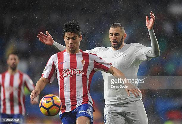 Karim Benzema of Real Madrid CF is beaten to the ball by Jorge Mere of Real Sporting de Gijon during the La Liga match between Real Madrid CF and...