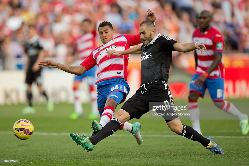 Karim Benzema of Real Madrid CF scores their third goal as Jeison Murillo of Granada CF tries to stop it during the La Liga match between Granada CF...