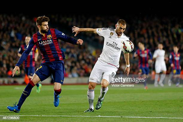 Karim Benzema of Real Madrid competes for the ball with Gerard Pique of FC Barcelona during the La Liga match between FC Barcelona and Real Madrid CF...