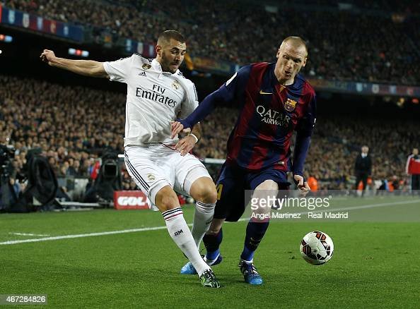 Karim Benzema of Real Madrid competes for the ball with Jeremy Mathieu of FC Barcelona during the La Liga match between FC Barcelona and Real Madrid...