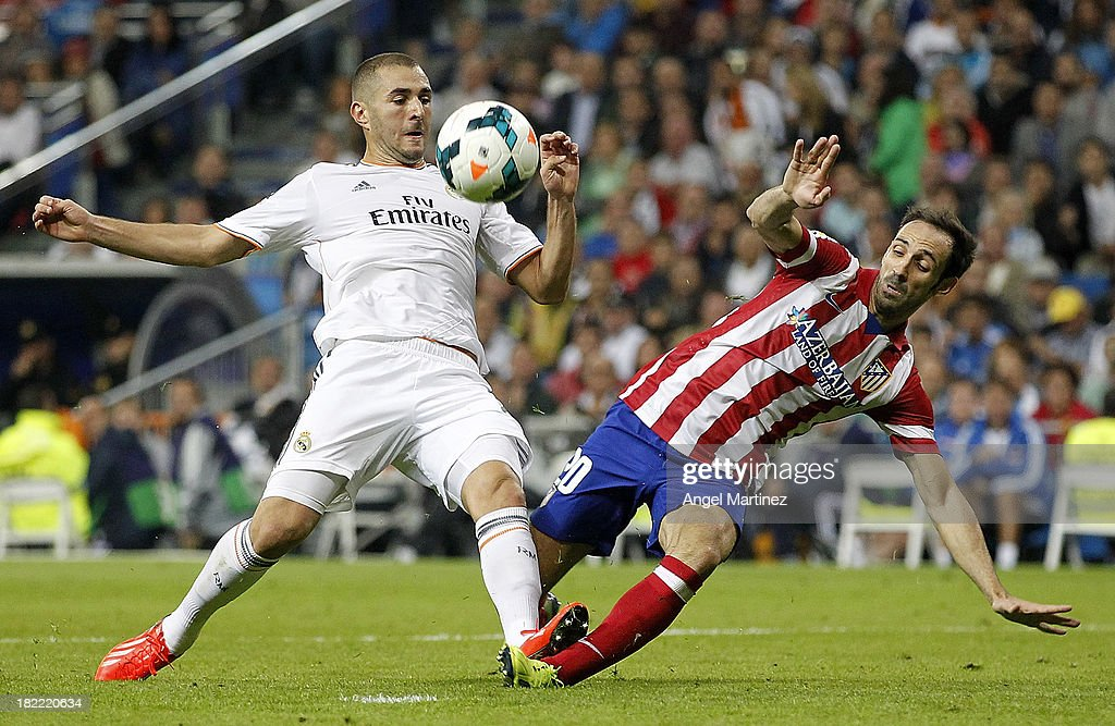 Karim Benzema of Real Madrid competes for the ball with Juanfran Torres of Atletico de Madrid during the La Liga match between Real Madrid and Club Atletico de Madrid at Estadio Santiago Bernabeu on September 28, 2013 in Madrid, Spain.