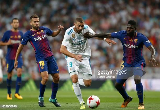 Karim Benzema of Real Madrid duels for the ball with Jordi Alba and Samuel Umtiti of FC Barcelona during the Supercopa de Espana Final second leg...