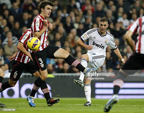 Karim Benzema of Real Madrid scores his side third goal past Jon Aurtenetxe of Athletic Club during the La Liga match between Real Madrid and...