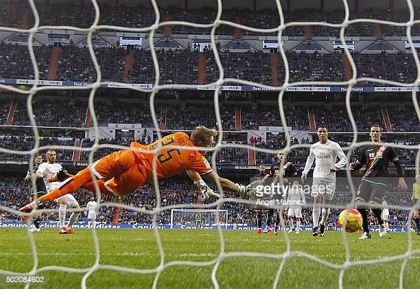 Karim Benzema of Real Madrid scores his team's nineth goal past Yoel Rodriguez of Rayo Vallecano during the La Liga match between Real Madrid CF and...
