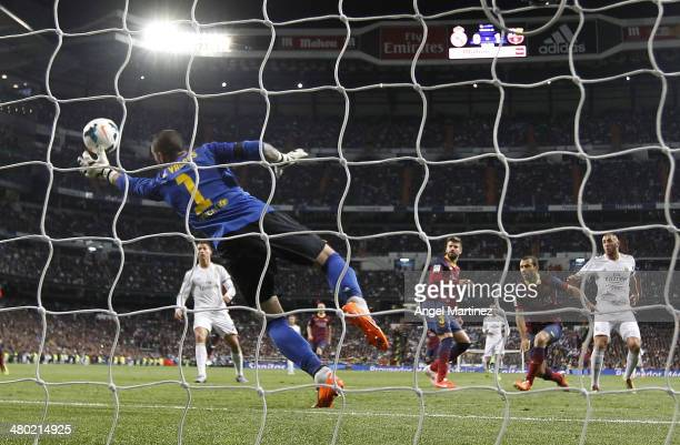 Karim Benzema of Real Madrid scores his team's past Victor Valdes of Barcelona during the La Liga match between Real Madrid and FC Barcelona at...