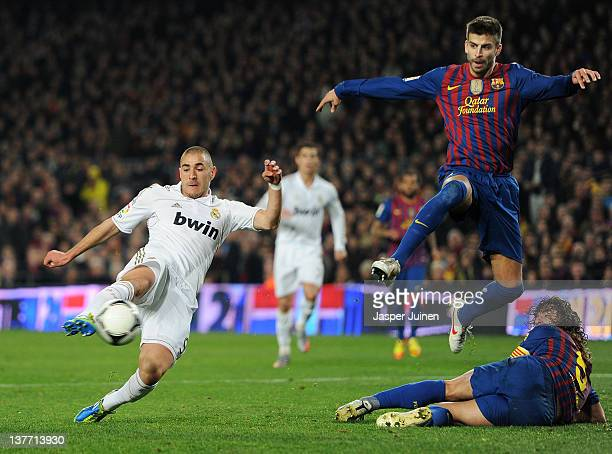 Karim Benzema of Real Madrid scores the equalizing goal past Gerard Pique and Carles Puyol of FC Barcelona during the Copa del Rey quarter final...
