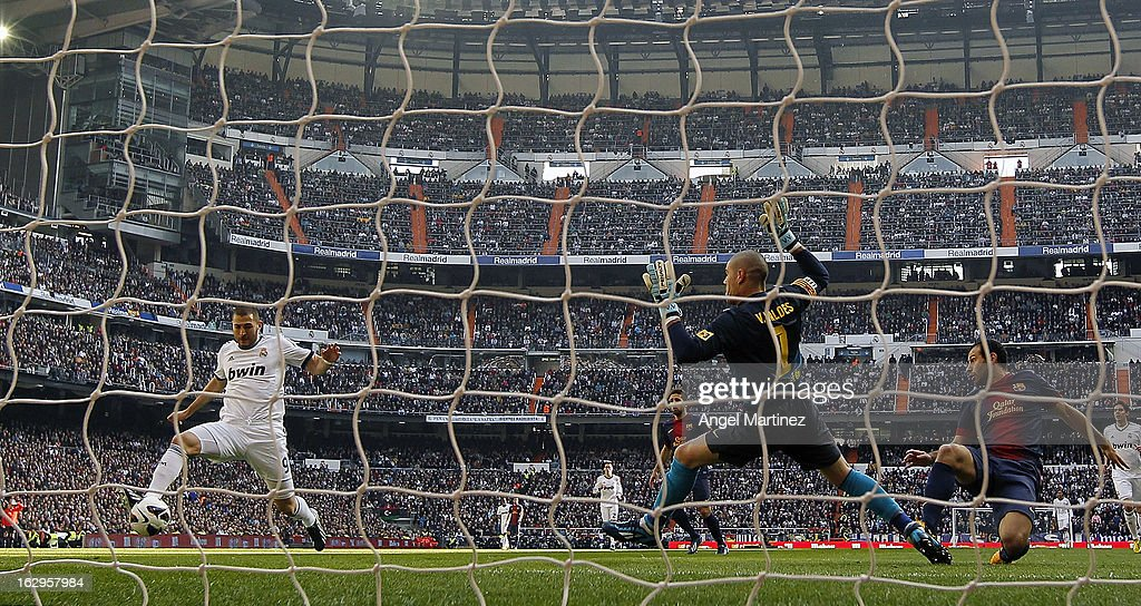 <a gi-track='captionPersonalityLinkClicked' href=/galleries/search?phrase=Karim+Benzema&family=editorial&specificpeople=796089 ng-click='$event.stopPropagation()'>Karim Benzema</a> (L) of Real Madrid scores the opening goal past goalkeeper <a gi-track='captionPersonalityLinkClicked' href=/galleries/search?phrase=Victor+Valdes&family=editorial&specificpeople=552392 ng-click='$event.stopPropagation()'>Victor Valdes</a> (C) and <a gi-track='captionPersonalityLinkClicked' href=/galleries/search?phrase=Javier+Mascherano&family=editorial&specificpeople=490876 ng-click='$event.stopPropagation()'>Javier Mascherano</a> of Barcelona during the La Liga match between Real Madrid and FC Barcelona at Estadio Santiago Bernabeu on March 2, 2013 in Madrid, Spain.