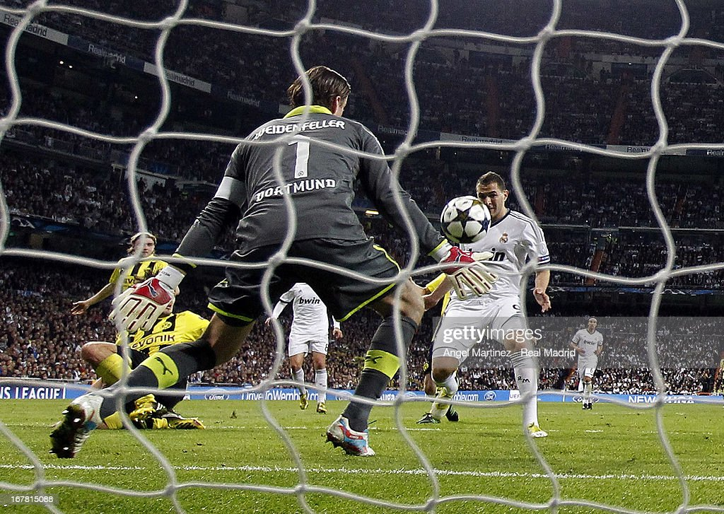 <a gi-track='captionPersonalityLinkClicked' href=/galleries/search?phrase=Karim+Benzema&family=editorial&specificpeople=796089 ng-click='$event.stopPropagation()'>Karim Benzema</a> of Real Madrid scores the opening goal past <a gi-track='captionPersonalityLinkClicked' href=/galleries/search?phrase=Roman+Weidenfeller&family=editorial&specificpeople=726753 ng-click='$event.stopPropagation()'>Roman Weidenfeller</a> of of Borussia Dortmund during the UEFA Champions League Semi Final second leg match between Real Madrid and Borussia Dortmund at Estadio Santiago Bernabeu on April 30, 2013 in Madrid, Spain.