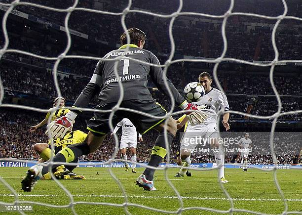 Karim Benzema of Real Madrid scores the opening goal past Roman Weidenfeller of of Borussia Dortmund during the UEFA Champions League Semi Final...