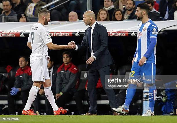 Karim Benzema of Real Madrid shakes hands with head coach Zinedine Zidane during the La Liga match between Real Madrid CF and Real CD Espanyol at...