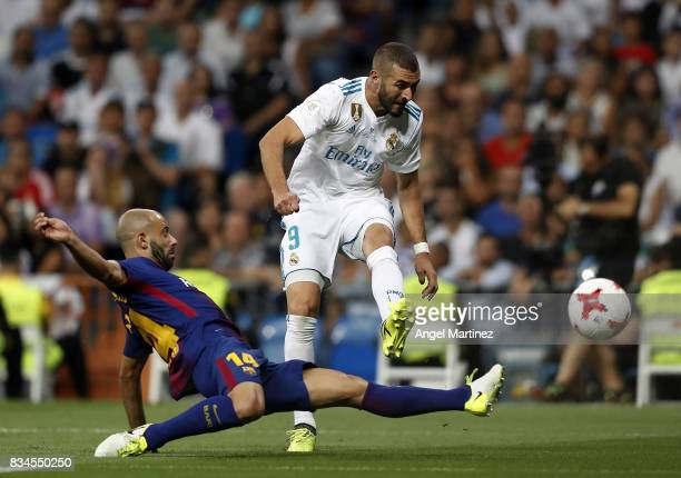 Karim Benzema of Real Madrid shoots on goal past Javier Mascherano of FC Barcelona during the Supercopa de Espana Final second leg match between Real...