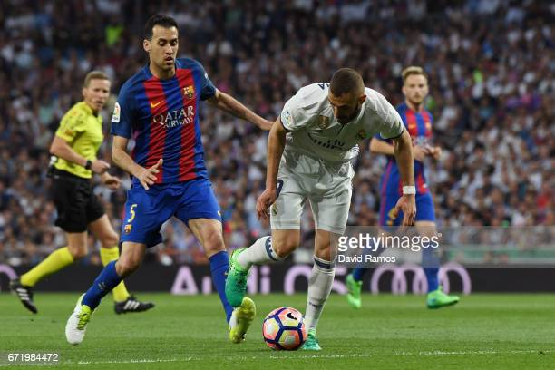 Karim Benzema of Real Madrid takes on Sergio Busquets of Barcelona during the La Liga match between Real Madrid CF and FC Barcelona at Estadio...