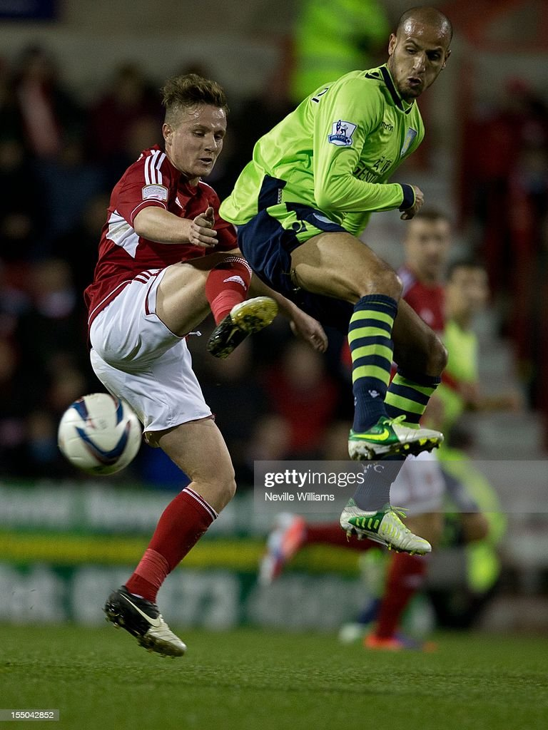 Karim El Ahmadi of Aston Villa is challenged by Simon Ferry (L) of Swindon Town during the Capital One Cup Fourth Round match between Swindon Town and Aston Villa at the County Ground on October 30, 2012 in Swindon, England.