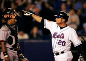 Karim Garcia of the New York Mets points to the crowd after he hit a solo home run to tie the game 11 against catcher Yorvit Torrealba and the rest...