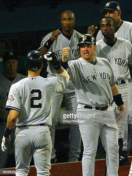 Karim Garcia of the New York Yankees and teammates celebrate Derek Jeter's scoring on a single by Hideki Matsui in the the eighth inning against the...