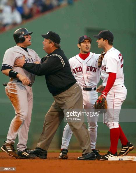 Karim Garcia of the New York Yankees is held back by the second base umpire after sliding into Todd Walker of the Boston Red Sox during Game 3 of the...