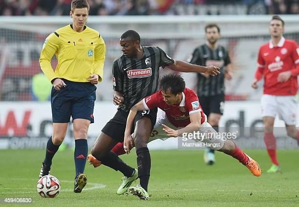 Karim Guede of Freiburg and Shinji Okazaki of Mainz compete for the ball during the Bundesliga match between FSV Mainz 05 and SC Freiburg at Coface...