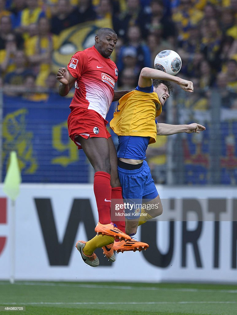 Karim Guede (L) of Freiburg challenges Benjamin Kessel of Braunschweig during the Bundesliga match between SC Freiburg and Eintracht Braunschweig at Mage Solar Stadium on April 12, 2014 in Freiburg, Germany.