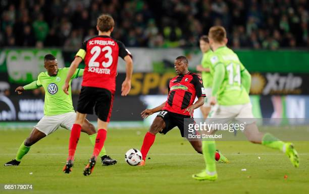 Karim Guede of Freiburg is challenged by Riechedly Bazoer of VfL Wolfsburg during the Bundesliga match between VfL Wolfsburg and SC Freiburg at...