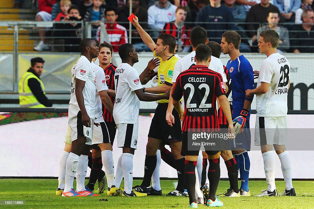 Karim Guede (L) of Freiburg is sent off by referee <a gi-track='captionPersonalityLinkClicked' href=/galleries/search?phrase=Felix+Brych&family=editorial&specificpeople=707645 ng-click='$event.stopPropagation()'>Felix Brych</a> during the Bundesliga match between Eintracht Frankfurt and SC Freiburg at Commerzbank-Arena on September 30, 2012 in Frankfurt am Main, Germany.