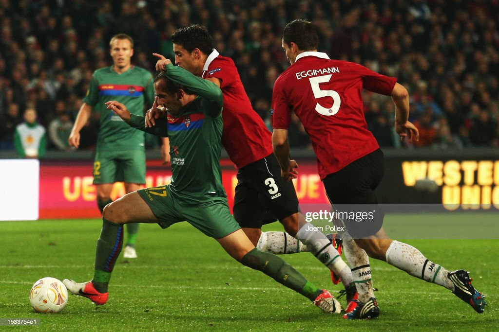 Karim Haggui (C) of Hannover and Theofanis Gekas (L) of Levante compete for the ball during the UEFA Europa League Group L match between Hannover 96 and Levante UD at AWD Arena on October 4, 2012 in Hannover, Germany.