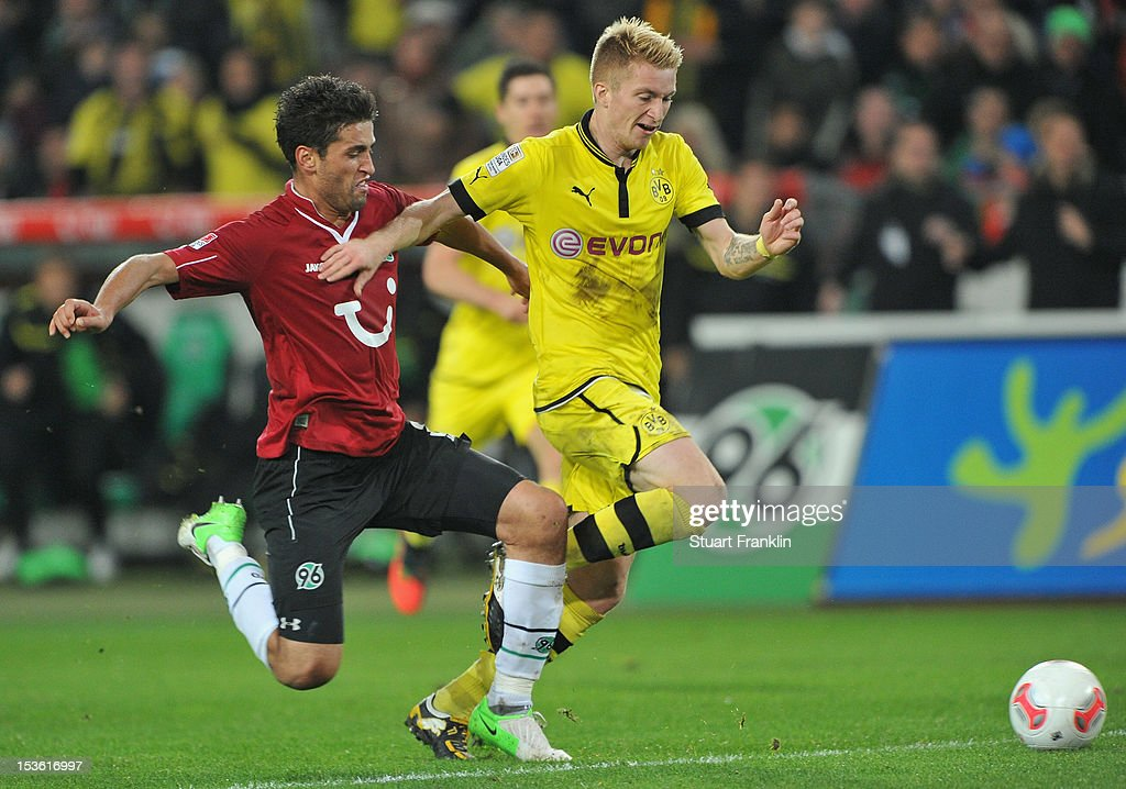 Karim Haggui of Hannover challenges Marco Reus of Dortmund during the Bundesliga match between Hannover 96 and Borussia Dortmund at AWD Arena on...