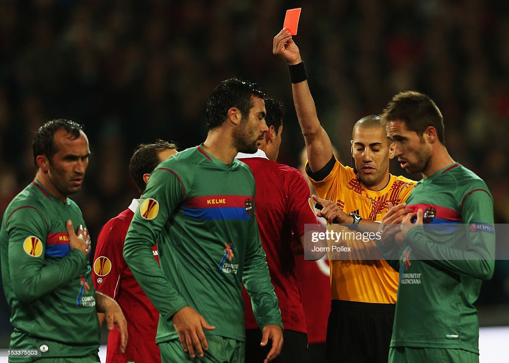 Karim Haggui (4th L) of Hannover gets the red card from referee Liran Liany during the UEFA Europa League Group L match between Hannover 96 and Levante UD at AWD Arena on October 4, 2012 in Hannover, Germany.