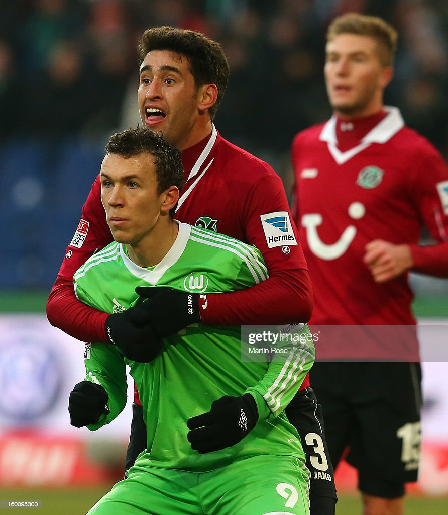 Karim Haggui (back) of Hannover holds Ivan Perisic (back) of Wolfsburg during the Bundesliga match between Hannover 96 and VfL Wolfsburg at AWD Arena on January 26, 2013 in Hannover, Germany.