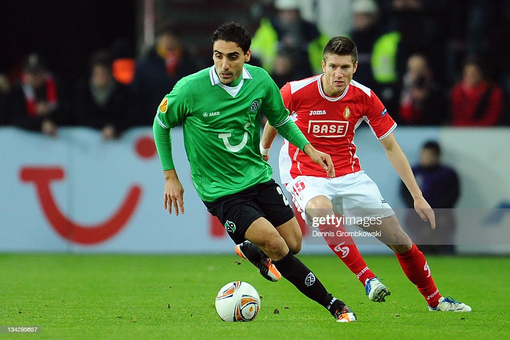 Karim Haggui of Hannover is chased by Sebastien Pocognoli of Liege during the UEFA Europa League group B match between R Standard de Liege and...