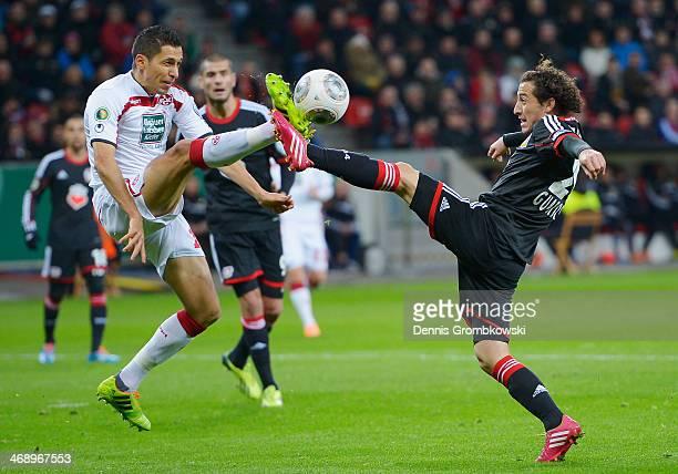 Karim Matmour of 1 FC Kaiserslautern and Guardado Hernandez of Bayer Leverkusen battle for the ball during the DFB Cup quarterfinal match between...