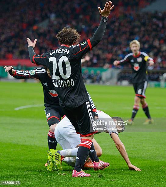 Karim Matmour of 1 FC Kaiserslautern is challenged by Guardado Hernandez and Gonzalo Castro of Bayer Leverkusen during the DFB Cup quarterfinal match...