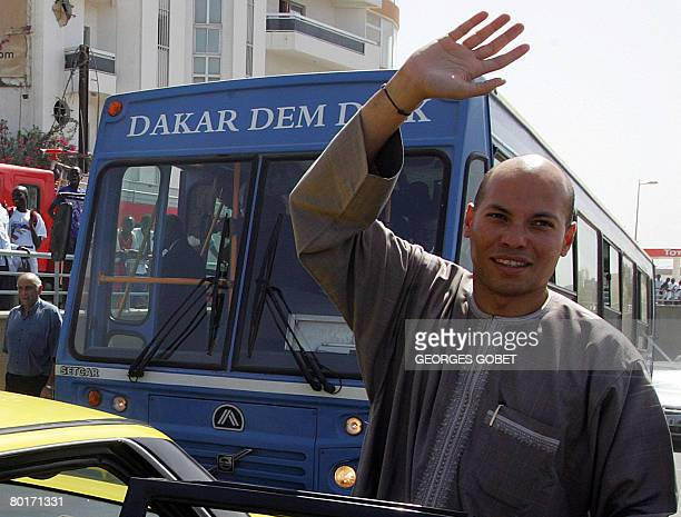 Karim Wade son of Senegalese president Abdoulaye Wade and president of ANOCI greets the public upon arrival for the inauguration of the Soumbedioune...
