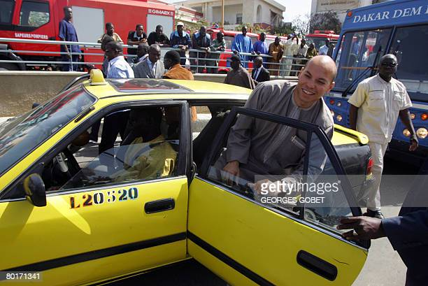 Karim Wade son of Senegalese president Abdoulaye Wade and president of ANOCI leaves a taxi upon arrival for the inauguration of the Soumbedioune...