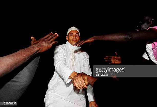 Karim Wade son of the former President of Senegal Abdoulaye Wade and a former minister in his government greets supporters as he leaves a police...
