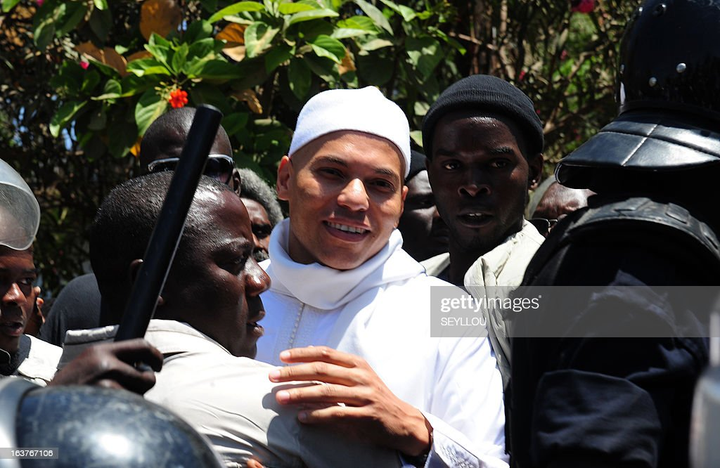 Karim Wade (white), the son of former Senegal President, leaves on March 15, 2013 after appearing before the west African nation's top anti-corruption prosecutor in Dakar, to justify his income against 'illegal wealth' accusations. Several leaders of the 2000-2012 Abdoulaye Wade regime, including his son Karin, have been repeatedly questioned by police and judges investigating allegations of 'illegal enrichment' but this is the first time Wade junior has been summoned by anti-corruption prosecutor Alioune Ndao.