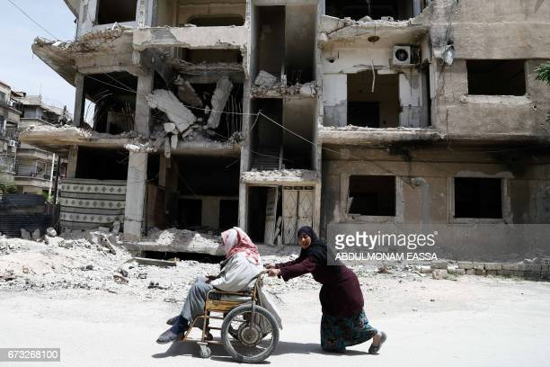 Karima 45yearsold pushes her 69yearold husband Abu Hussein in a wheel chair past destroyed buildings in the rebelcontrolled town of Hamouria in the...