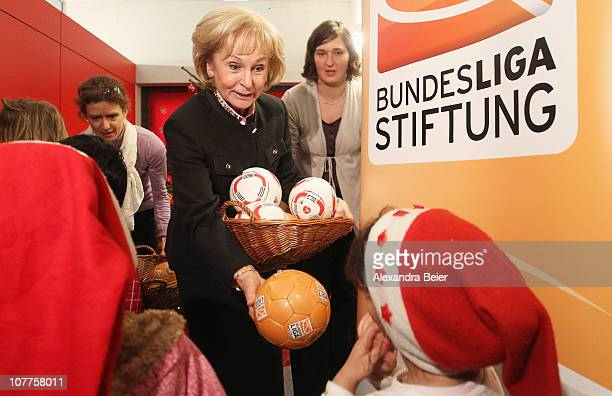Karin Stoiber wife of former Bavarian Governor and curator of the DFL Foundation Edmund Stoiber hands over a soccer ball to a child of the social...