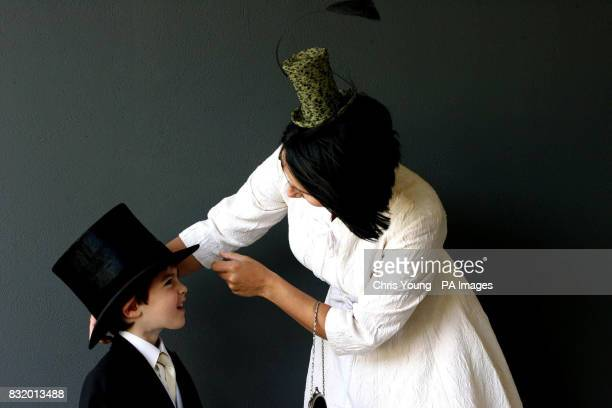 Karina Tracey helps her four year old son Charles with his hat at the Royal Ascot race meeting at Ascot racecourse in Berkshire during Ladies Day