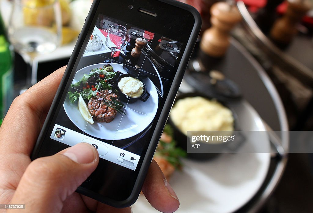 Karine ALBERTAZZI et Isabelle TOUSSAINT A man takes a picture of his meal with his mobile phone to share it on the 'Food Reporters' network on July 19, 2012 during his lunch in a restaurant in Paris. 'Food Reporters' is a culinary social network accessible via a smartphone application and a website.