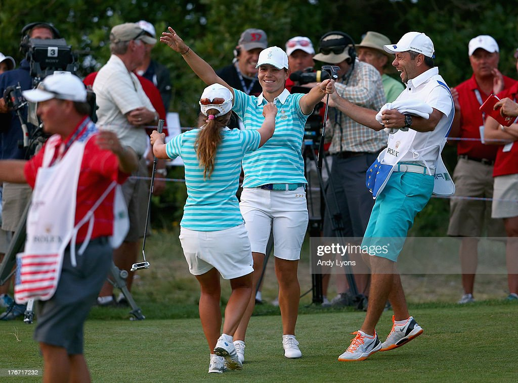 Karine Icher of France and Beatriz Recari of Spain and the European Solheim Cup Team celebrate after Icher made a putt to win their match during the...