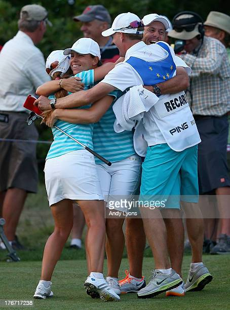 Karine Icher of France and Beatriz Recari of Spain and the European Solheim Cup Team and their caddies celebrate after Icher made a putt to win their...