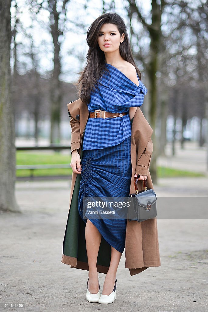 Karine Somerset poses wearing an Awake coat Prada dress and Celine shoes before the Valentino show at the Jardin des Tuileries during Paris Fashion...