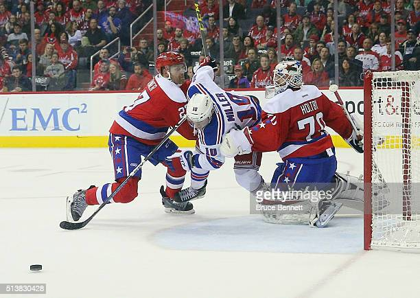 Karl Alzner and Braden Holtby of the Washington Capitals defend the net against JT Miller of the New York Rangers at the Verizon Center on March 4...